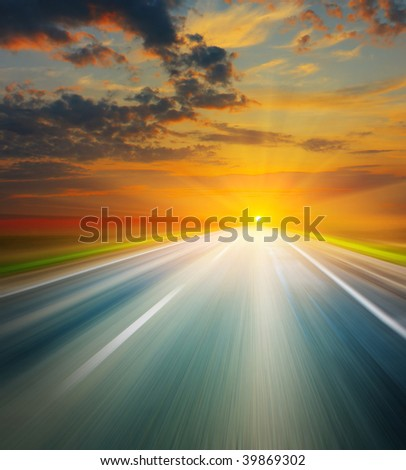 Empty blurry road under sunset light with clouds - stock photo