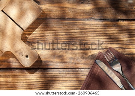 Empty board with fork and knife on wooden table. Top view - stock photo