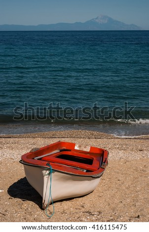 Empty Boat on the Seashore in Summer with the View to the Athos, Ionic Sea, Sithonia, Chalkidiki, Greece - stock photo