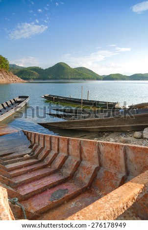 Empty boat standing at pier under bright sunlight with beautiful scenery for background usage
