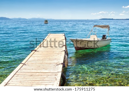 Empty boat standing at wooden pier under bright sunlight with shadow on pebbles at sea floor seen through transparent water, Corfu, Greece - stock photo