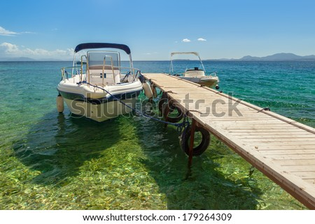 Empty boat standing at wooden pier under bright sunlight with shadow on pebbles at sea floor seen through transparent water of Ionian sea, Corfu, Greece