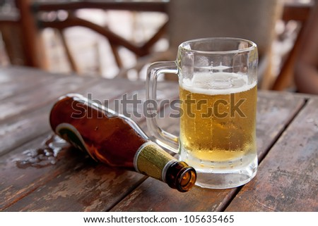Empty bottle and the glass of beer on wooden table - stock photo