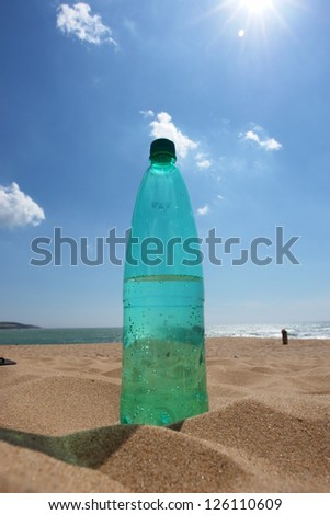 empty Bottle in the beach sand outside - stock photo