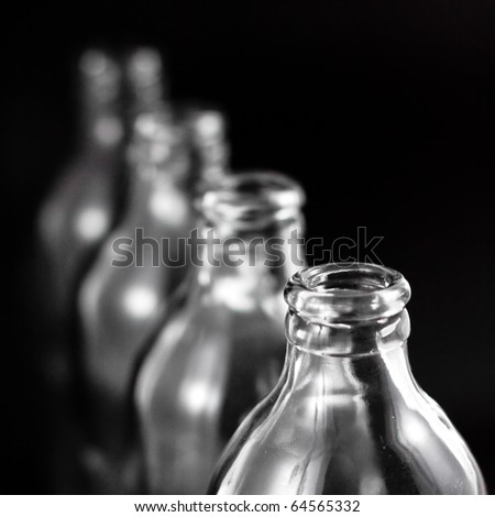 empty bottles collection, colorless, isolated on black background - stock photo