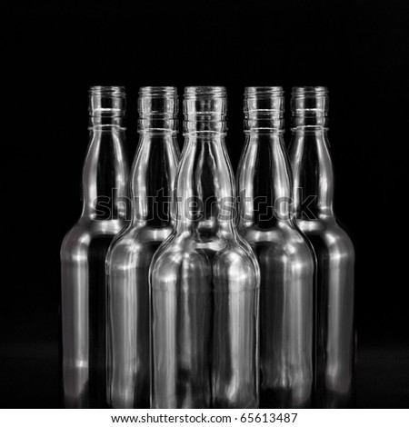 empty bottles collection, colorless, isolated on black backgrounde - stock photo