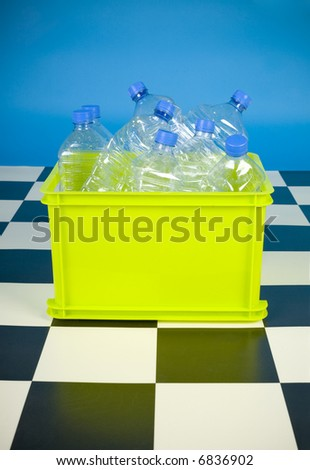 Empty bottles in green bin. Front view - stock photo