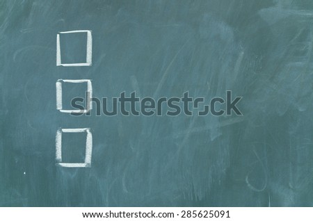 Empty boxes on green chalkboard - stock photo