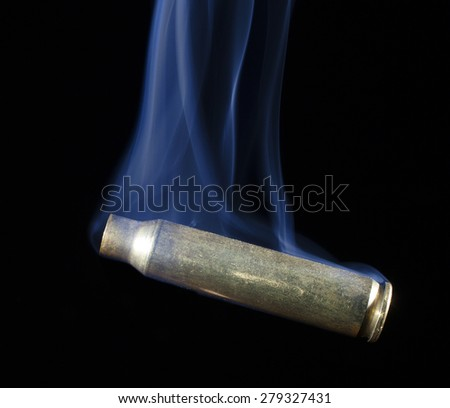 Empty brass shell with blue smoke rising from its sides - stock photo