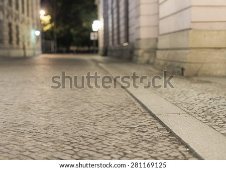 empty brick road at night with blurred background, historic midtown of Berlin, Germany, Europe - stock photo