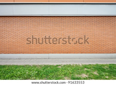 Empty brick wall and green grass ground. - stock photo