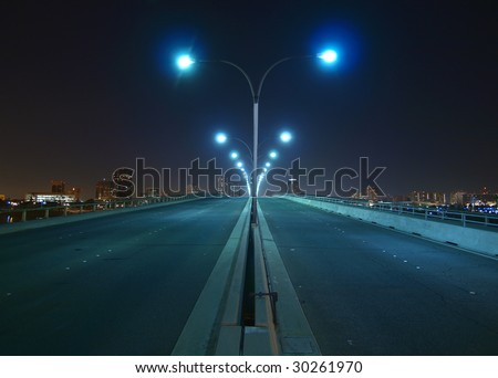 Empty bridge, towers and street lights at night.
