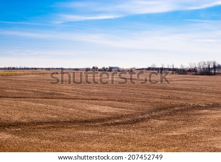 Empty brown farm fields with barn in distance against partly cloudy sky. - stock photo