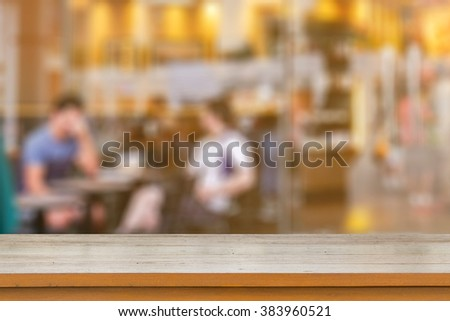 Empty brown wooden table and Coffee shop interior with some people meeting blur background with bokeh image, for product display montage,can be used for montage or display your products,vintage color - stock photo