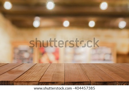 Empty brown wooden table and Coffee shop interior with some people meeting blur background with bokeh image, for product display montage,can be used for montage or display your products - stock photo