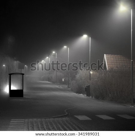 Empty bus shelter in suburban area on dark foggy evening