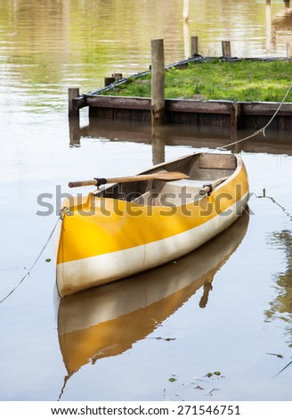 Empty canoe moored in calm lake - stock photo