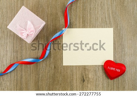 Empty card with heart and gift box on wooden background - stock photo