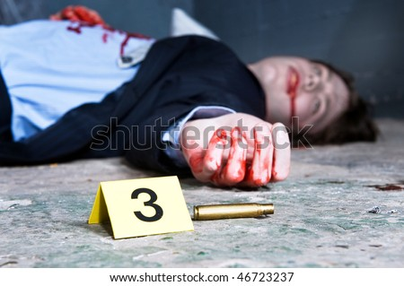 Empty cartridge found on a crime scene with a yellow placard with number three and a dead body in the background - stock photo