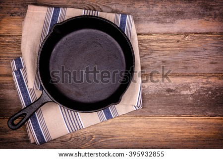 Empty cast iron skillet with tea towel, over old wood background. Retro style processing and space for your text.  - stock photo