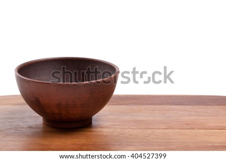 Empty ceramic bowl on wooden kitchen table. Isolated on white background. - stock photo