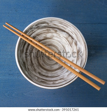 Empty ceramic bowl with bamboo chopsticks over blue wooden surface. Top view. Square image - stock photo