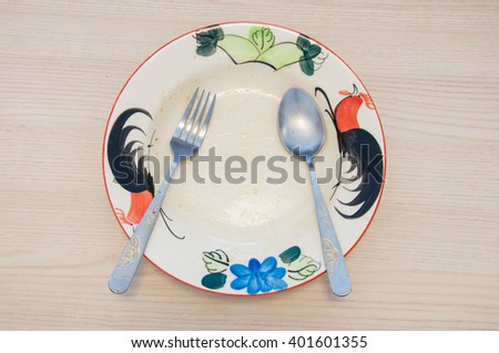 empty ceramic plate with fork and spoon after food is eaten, nothing left - stock photo