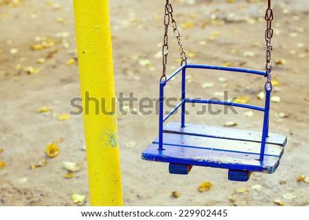 Empty chain swing on autumnal kids playground - stock photo