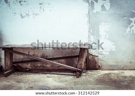 Empty chair and grungy wall - stock photo