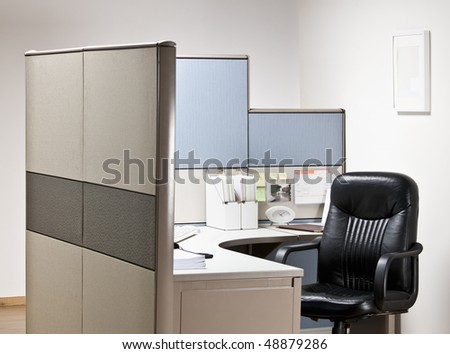 Empty chair at desk in cubicle - stock photo