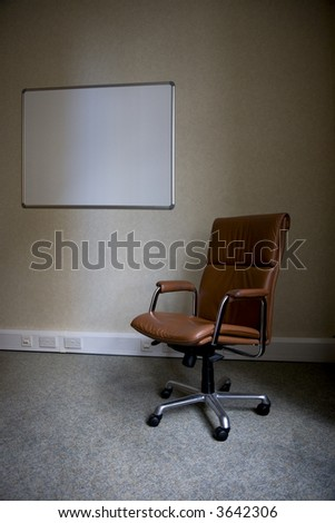 Empty chair in a deserted office with blank whiteboard - stock photo