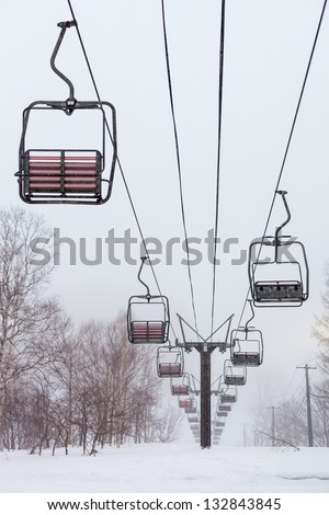 Empty chair lift in the mist and snow at Niseko ski resort in Japan. Shallow depth of field.