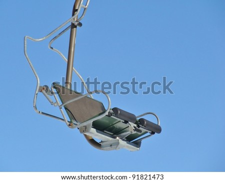 Empty chairlift against blue sky