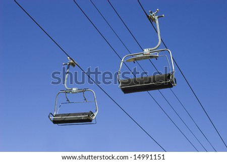 empty chairlifts on a blue sky background - stock photo