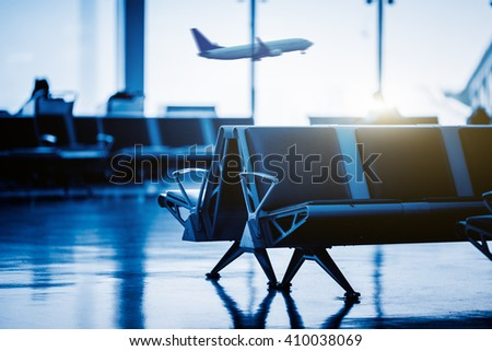 Empty chairs in the departure hall at airport , with  an airplane taking off at sunset. blue toned. - stock photo