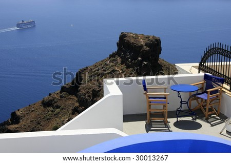 Empty chairs set on a hill overlooking the sea. - stock photo