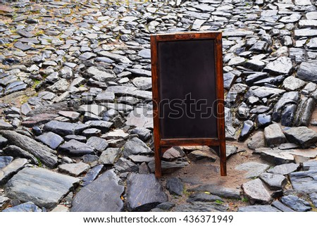 Empty chalkboard or blackboard on the street with copyspace. Blank menu board with space for text. - stock photo