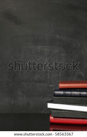 Empty chalkboard with books - stock photo