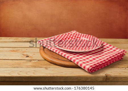 Empty checked plate and tablecloth on wooden table - stock photo