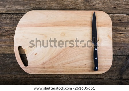 Empty chopping board with a sharp paring knife on a distressed grunge wooden table in a rustic kitchen, overhead view with a vignette and copyspace - stock photo