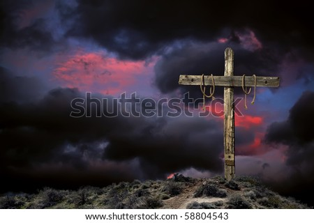 Empty Christian cross against angry cloudy sky representing the immediate aftermath of the crucifixion of Jesus Christ. - stock photo