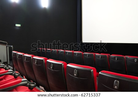 Empty cimema with red seats and white screen