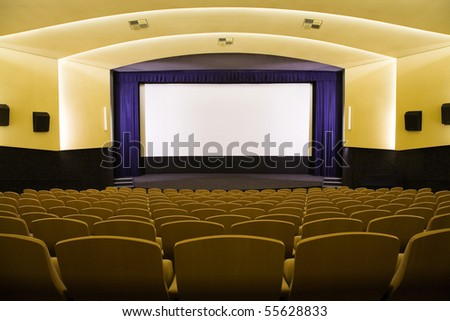 Empty cinema auditorium with line of chairs and projection screen. Ready for adding your own picture. Front view. - stock photo
