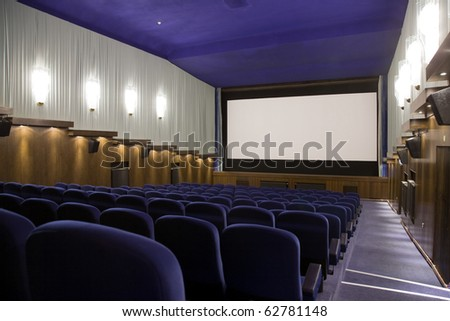 Empty cinema auditorium with line of chairs and projection screen. Ready for adding your own picture. Right side view.