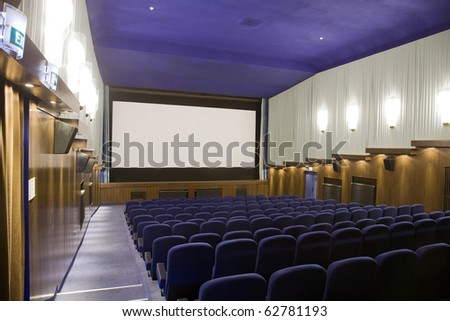 Empty cinema auditorium with line of chairs and projection screen. Ready for adding your own picture. Left side view. - stock photo