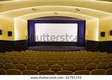 Empty cinema auditorium with line of chairs and projection screen. Ready for adding your own picture. Front view.