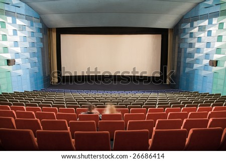 Empty cinema auditorium with line of red chairs, sitting visitors and silver screen. Ready for adding your own picture.