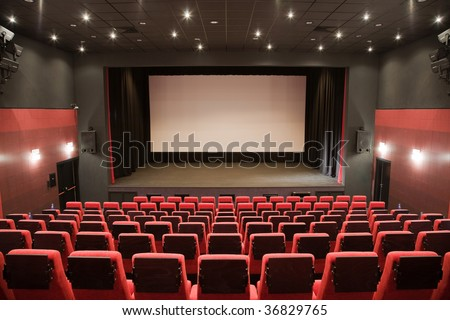 Empty cinema auditorium with line of red chairs, stage and projection screen. Ready for adding your own picture. - stock photo