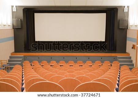 Empty cinema auditorium with line of wooden chairs and projection screen. Ready for adding your own picture.
