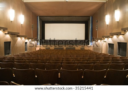 Empty cinema auditorium with row of chairs and projection screen. Ready for adding your own picture. - stock photo